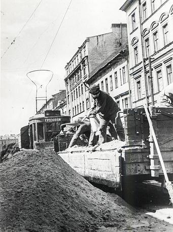 Разгрузка песка из грузового трамвая для оборонных целей.