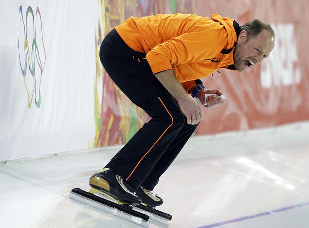 Герард Кемкерс поддерживает голландского конькобежца Свена Крамера во время забега на 5000 м