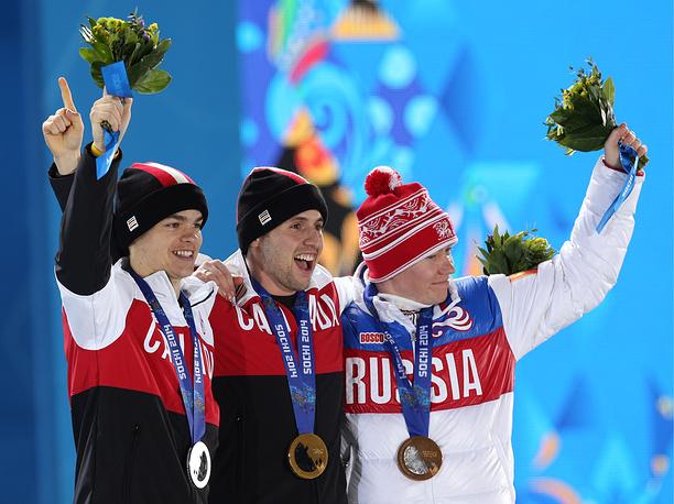 Канадцы Микаэль Кингсбери (серебряная медаль), Александр Билодо (золотая медаль) и россиянин Александр Смышляев (бронзовая медаль) (слева направо) победившие в могуле во время соревнований по фристайлу среди мужчин