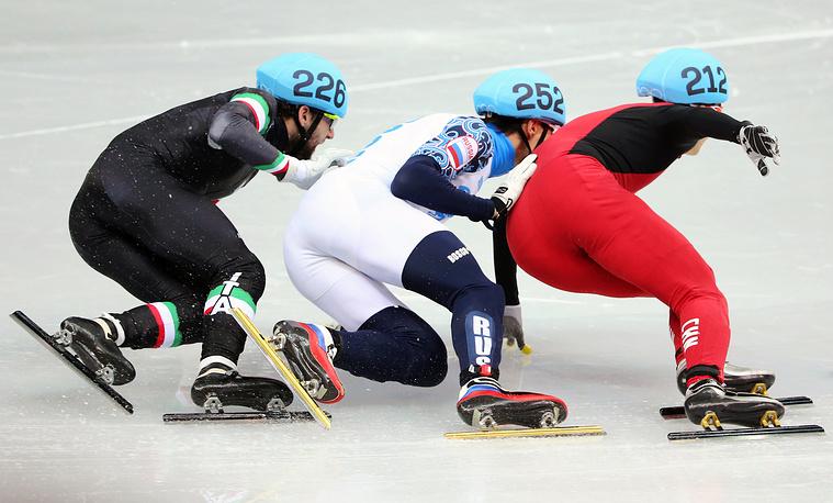 Россиянин Владимир Григорьев в окружении итальянца Юрия Конфронтолы (слева) и китайца У Дацзина (справа) в четвертьфинальном забеге на 1000 м