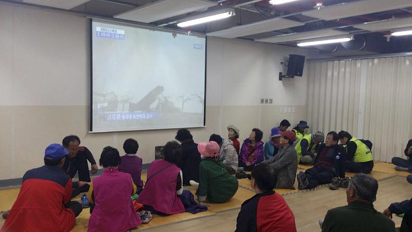 Жители острова Пэннёндо смотрят репортаж о проводимых КНДР артиллерийских стрельб в Желтом море. 31 марта 2014 года