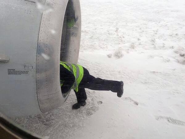 В Кольцово во время снегопада. Сотрудник аэропорта чистит компрессор турбины самолета от снега