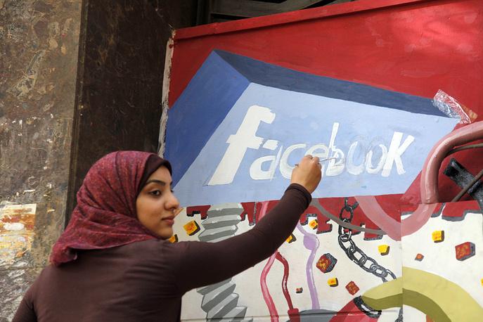 Изображение логотипа Facebook на панно в честь египетской революции на стене Хелуанского университета искусств