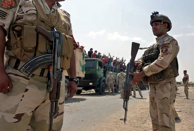 Четыре военных грузовика перевозят иракских добровольцев на базу Мутанна в центре Багдада