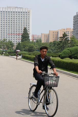 В отличие от многих азиатских столиц, где пешеходы уже давно пересели на велосипеды, для Пхеньяна это явление сравнительно новое: до 1992 года передвигаться на велосипедах по городу было официально запрещено - власти считали, что без велосипедов бескрайние пхеньянские улицы выглядят намного лучше