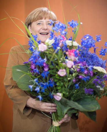Ангела Меркель с букетом от министра финансов Вольфганга Шойбле по случаю дня рождения. 2013 год