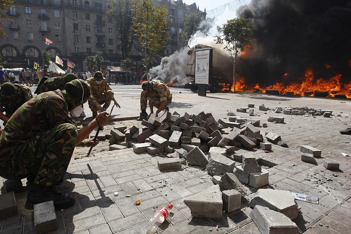 """В четверг коммунальные службы Киева приступили к разбору баррикад на Крещатике и прилегающих улицах, после чего активисты """"майдана"""" начали бросать в коммунальщиков бутылки и камни"""