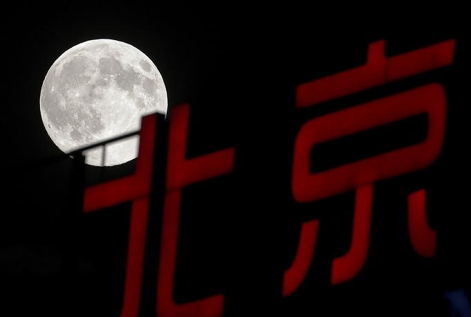 Вывеска на фоне полной луны в Пекине