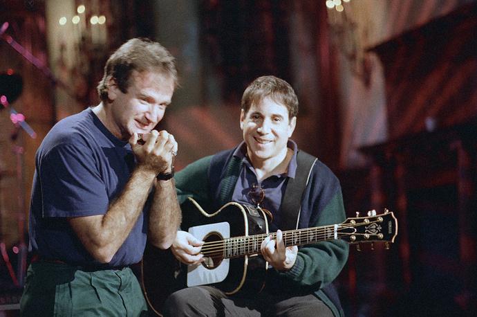 Робин Уильямс играет на губной гармошке в шоу Saturday Night Live на канале NBC. Справа музыкант Пол Саймон играет на гитаре. Нью-Йорк, 1986 год