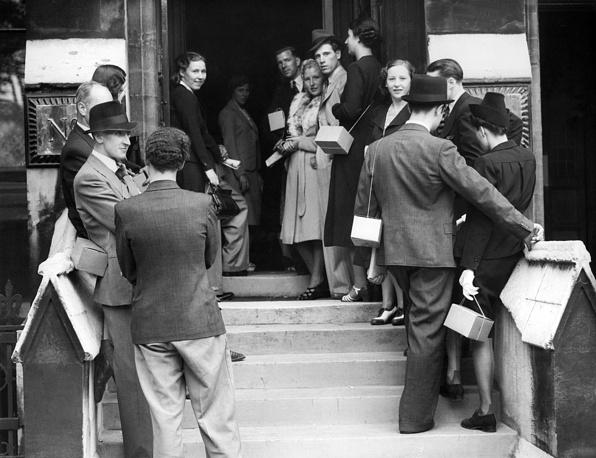 Объявление войны вызвало в Великобритании свадебный бум. Очередь из желающих пожениться в Лондоне. Почти у всех с собой противогазы. 4 сентября 1939 года