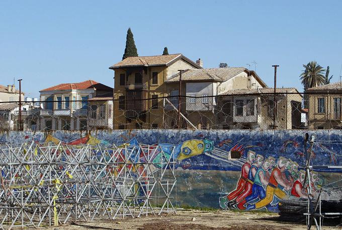 """Стена, которая проходит через столицу Кипра Никосию, появилась в результате военного вторжения Турции и оккупации северной части острова. Конструкция является частью «зеленой линии» - буферной зоны между территориями, контролируемыми противостоящими сторонами. Длина """"зеленой линии"""" составляет 180 км, ширина в некоторых районах - 7 км"""