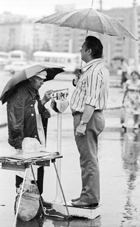 Мужчина взвешивается на уличных весах под дождем, 1981 год