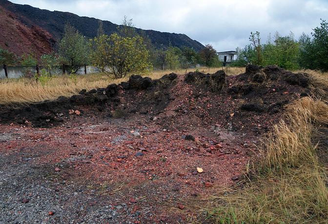 Первоначально были обнаружены тела четырех человек. Затем власти ДНР сообщили, что в одном из трех найденных захоронений лежат тела мирных жителей, их обнаружили уже около сорока, в двух других - тела пленных ополченцев и украинских солдат. На фото: место захоронения на территории склада шахты