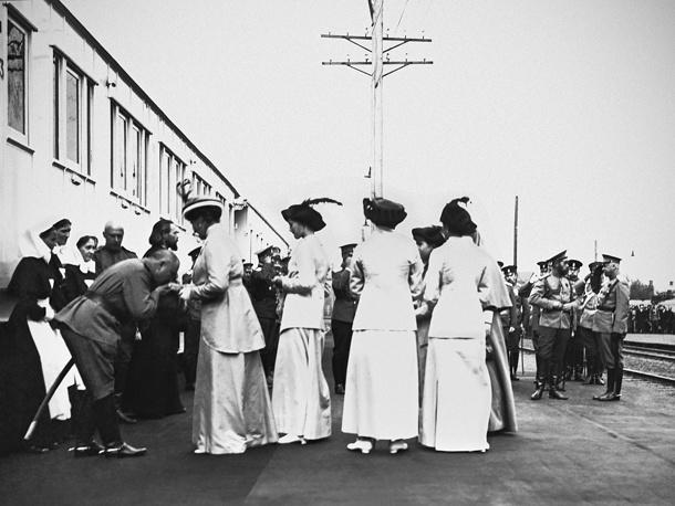 Император Николай II (на втором плане) с императрицей Александрой Федоровной и Великими княжнами у санитарного поезда на Казанском вокзале в Москве. 1914 год