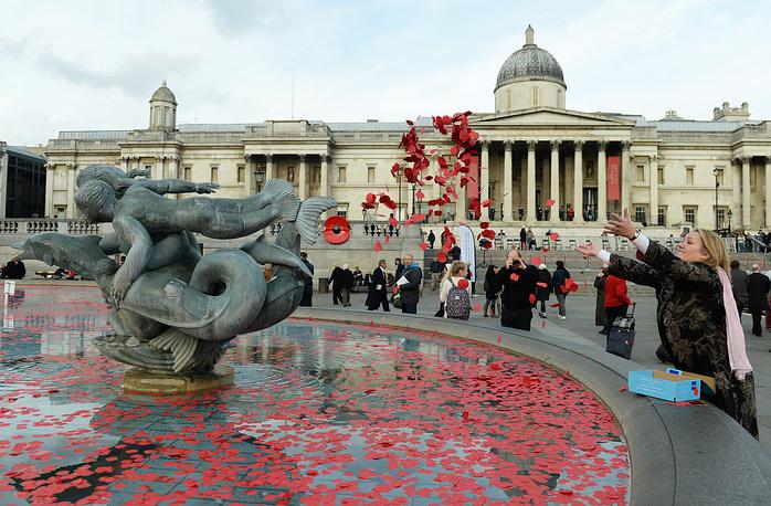 Женщина бросает маки в фонтан на Трафальгарской площади во время церемонии, посвященной годовщине подписания Компьенского перемирия, положившего конец военным действиям в Первой мировой войне