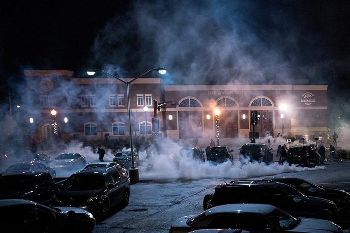 В общей сложности, по данным полиции, огнем охвачены 12 зданий и несколько автомобилей. На фото: столкновения полиции с демонстрантами возле пожарной станции в Фергюсоне