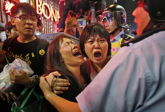 Судебные приставы при поддержке полиции Гонконга провели операцию по сносу баррикад, возведенных демонстрантами в районе Монгкок. Более ста человек, которые вступили в конфронтацию со стражами порядка и препятствовали этим работам, были задержаны. Протестующие требуют от Пекина отменить ограничения на выборах главы администрации Гонконга в 2017 году. На фото: протестующие в Гонконге, 26 ноября