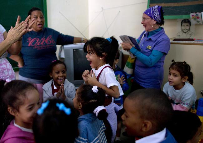 """Что касается торговых ограничений, как пояснил Обама, некоторые из них прописаны в законодательстве США, и глава Белого дома пообещал """"активно работать"""" с Конгрессом по вопросу снятия эмбарго. На фото: жители Гаваны радуются во время речи Рауля Кастро о нормализации отношений с США, 17 декабря 2014 года"""