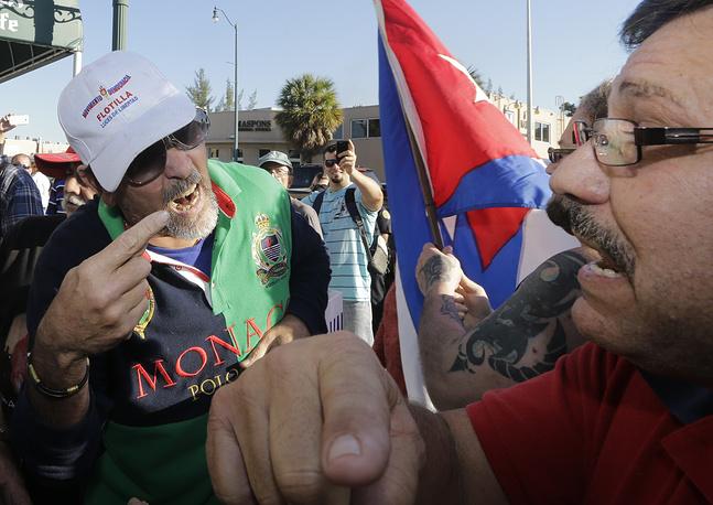 """Некоторые члены Конгресса США выступили с резким осуждением инициативы Обамы по налаживанию связей с Кубой. Так, спикер палаты представителей Джон Бейнер заявил, что """"отношения с режимом Кастро не должны быть пересмотрены, тем более нормализованы, пока народ Кубы не получит свободу, и ни секундой раньше"""". На фото: спор между сторонниками и противниками сотрудничества с Кубой, Майами, 17 декабря 2014 года"""