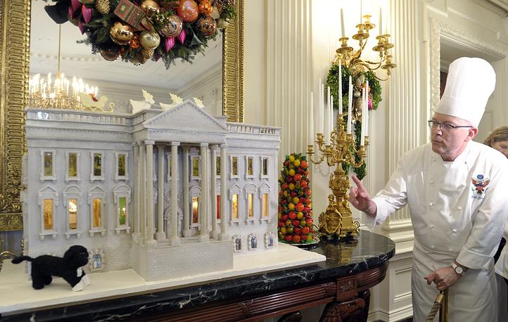 Кондитер Белого дома Билл Йоссес представляет макет пряничного дома с изображением пса семьи Обама - Бо и огорода первой леди, 2012 год