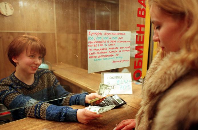 """По данным Госкомстата РФ, более одной пятой всех доходов россияне тратили на покупку иностранной валюты. В январе - апреле 1997 года гражданами России приобретено валюты в общей сложности на сумму 107,6 трлн руб. На фото: в пункте обмена валюты коммерческого банка """"Востокстройбанк"""" в Москве, 1997 год"""