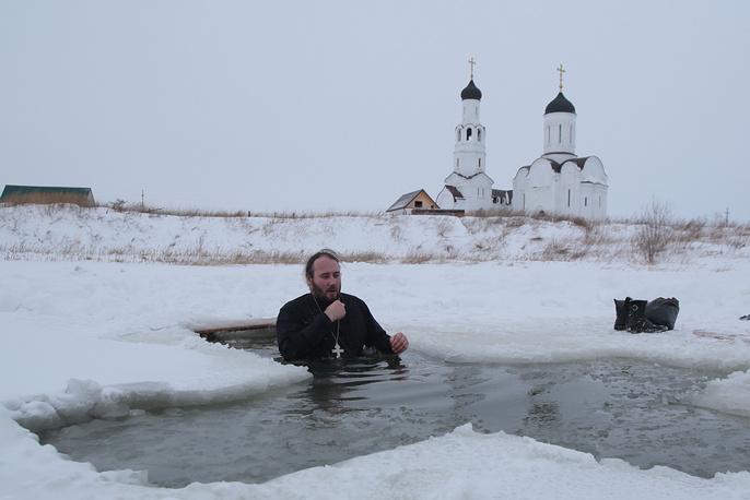 Настоятель храма князя Александра Невского отец Артемий окунается в прорубь на реке Мильтюш в селе Бурмистрово