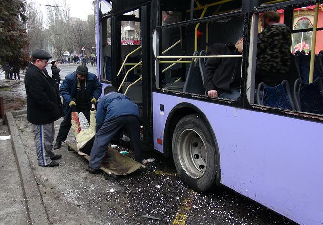 """22 января в Ленинском районе Донецка была обстреляна остановка общественного транспорта. Жертвами атаки стали, по уточненным данным, восемь человек, еще 17 получили ранения. На фото: эвакуация погибших из троллейбуса на остановке общественного транспорта """"Завод Боссе"""""""