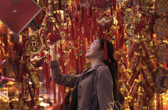 Считается, что в новогоднюю ночь важно хорошо встретить спускающихся с Неба богов. На фото: жительница Тайбея на одном из городских рынков