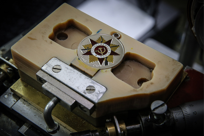 После этого заготовки отправляют на штамповку и контроль. Сотрудники предприятия тщательно осматривают все медали на предмет брака - царапины или затемнения. На фото: нанесение изображения методом тампонной печати