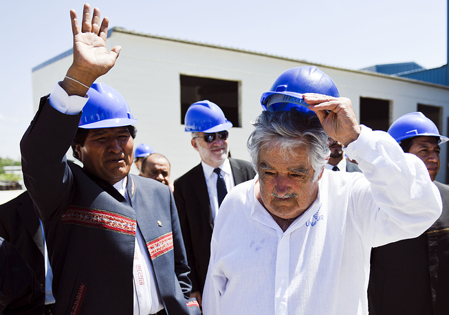 """Одним из самых значительных проектов Хосе Мухики стал так называемый план """"Вместе"""". Его цель - строительство доступного жилья для 15 тыс. семей, живущих в крайне неблагоприятных условиях. Программа была создана в мае 2010 года. Предполагалось, что к концу президентского срока Хосе Мухики удастся обеспечить жильем 4 тыс. семей, однако на февраль 2015 года готовы дома только для 1,5 тыс. семей, еще 1 тыс. находятся на стадии строительства. На фото: президент Боливии Эво Моралес (слева) и президент Уругвая Хосе Мухика на заводе по производству стекла, 26 февраля 2015 года"""