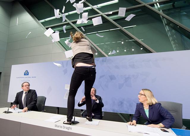 """15 апреля пресс-конференция главы ЕЦБ Марио Драги была прервана после того, как на него напала одна из присутствующих в зале. Девушка запрыгнула на стол банковского чиновника, выкрикивая протесты против """"диктатуры ЕЦБ"""". Общение с журналистами возобновилось в нормальном режиме через несколько минут после инцидента"""
