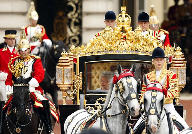 Церемония начинается с поездки Елизаветы II вместе с супругом принцем Филипом, герцогом Эдинбургским из Букингемского дворца в Вестминстерский дворец с эскортом конных гвардейцев. На фото: Елизавета II с супругом принцем Филипом, 2014 год
