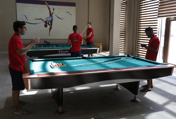 Спортсмены сборной Мальты играют в бильярд в Деревне атлетов