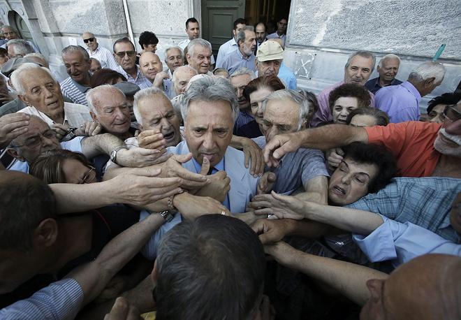 Министерство финансов Греции установило лимит на снятие наличных в банкоматах (€60 в день на человека), переводы денежных средств за границу были запрещены. На фото: толпа у банка в Афинах