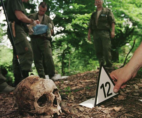 26 февраля 2007 года события в Сребренице были признаны геноцидом Международным судом ООН. На фото: финский судебно-медицинский эксперт рядом с черепом жертвы резни в Сребренице, найденного в холмах у деревни Кравицы (около 15 км к северо-западу от Сребреницы). 5 июля 1996 года