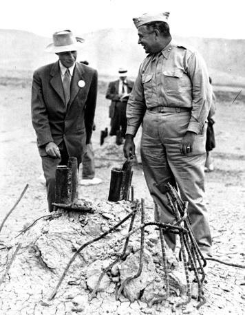 Научный руководитель Манхэттенского проекта американский физик-теоретик Роберт Оппенгеймер (слева) и военный руководитель программы по созданию ядерного оружия генерал-лейтенант армии США Лесли Ричард Гровс (справа) на испытательном полигоне после испытания бомбы