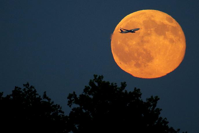 """Самолет взлетает на фоне """"Голубой луны"""", Нью-Йорк"""