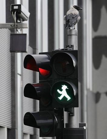 """В Германии сигналы светофора для пешеходов имеют оригинальную форму маленького """"светофорного"""" человечка - Ampelmännchen, который приобрел культовый статус. Предметы с его изображением стали популярными сувенирами у туристов. На фото: светофор в Берлине, Германия, 2009 год"""