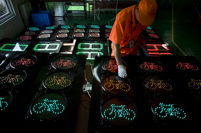 Специальные светофоры для регулирования движения велосипедов имеют меньший размер и устанавливаются на удобной для велосипедистов высоте. На фото: рабочий проверяет солнечные батареи в светофорах, Баодин, Китай, 2009 год