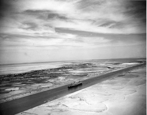 В 1875 г. и 1880 г. внешние долги вынудили Египет продать свою долю в канале Великобритании. Компания Суэцкого канала стала практически англо-французским предприятием. На фото: вид на Суэцкий канал, 1953 год