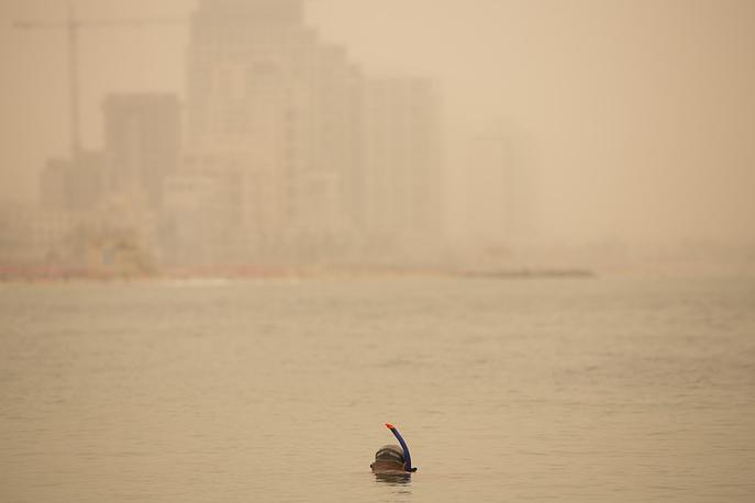 Мужчина ныряет с маской у побережья Средиземного моря в Тель-Авиве во время сильнейшей песчаной бури, которая накрыла весь Ближний Восток, 8 сентября