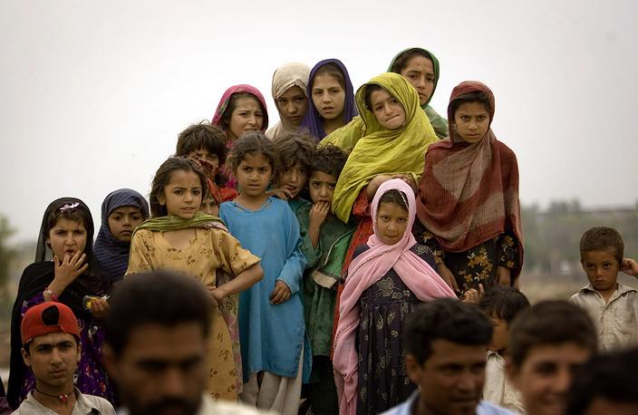 Каждая шестая девочка-подросток в мире в возрасте от 15 до 19 лет либо состоит в браке, либо фактически находится в семейном сожительстве. На фото: афганские девочки наблюдают за свадьбой в лагере для беженцев на окраине Исламабада, Пакистан, 2008 год