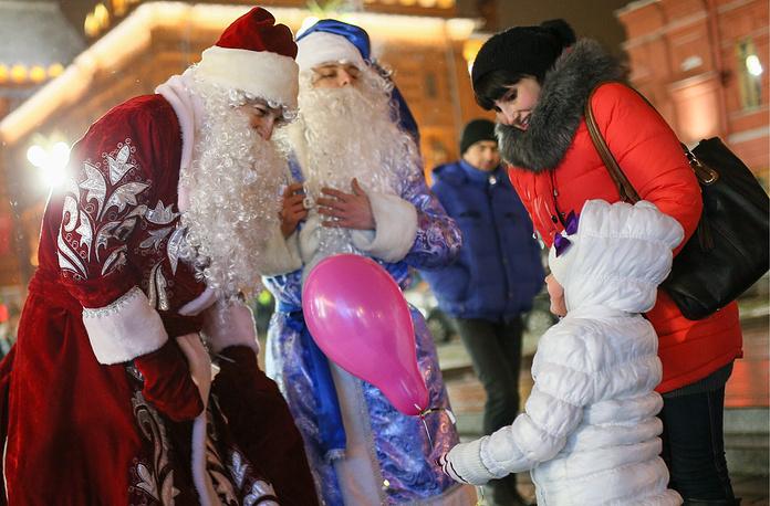 Москва. 1 января 2016. Деды Морозы поздравляют людей на Манежной площади.