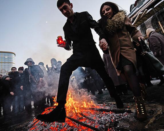 Члены армянской общины прыгают через символ праздника - костер
