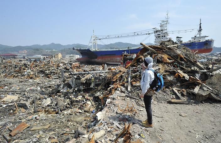 Юмико Огата (46) ищет свою мать Сейко Сато (68) в разрушенном цунами районе Шикари портового города Кесеннума, префектура Мияги, северная Япония, 15 апреля 2011 года