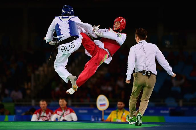 Россиянин Алексей Денисенко (слева) и иорданский спортсмен Ахмад Абугауш во время финального поединка на соревнованиях по тхэквондо в весовой категории до 68 кг
