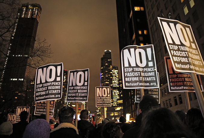 """Протестующие во главе с режиссером Майклом Муром несут таблички с надписями: """"Остановите фашистский режим Трампа/Пэнса прежде, чем он начнется"""""""