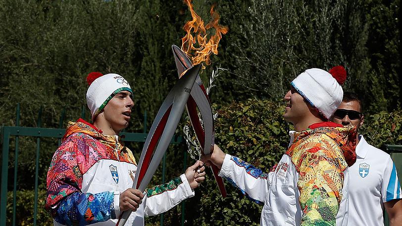 Яннис Антониу передает Олимпийский огонь Александру Овечкину. Фото EPA/DIMITRI MESSINIS / POOL