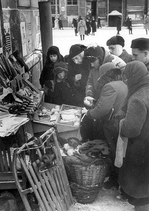 Жители блокадного Ленинграда у ларька с товарами.