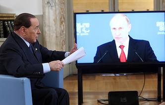 Former Italian Prime Minister Silvio Berlusconi is pictured next to a screen showing Russian President Vladimir Putin during an interview with Rai 3